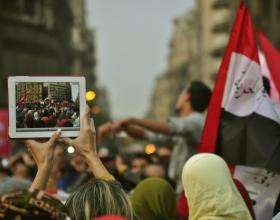 Source - © 2013 We Are Here, Courtesy of Photoshare, Description - Protesters wave a Egyptian flag as the activities during the Egyptian Revolution are captured on a tablet computer.