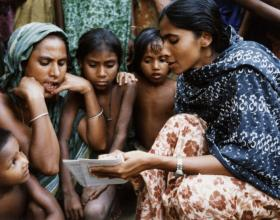 Source - © 1994 Cheryl Groff, Courtesy of Photoshare. A Family Welfare Assistant shares family planning information with villagers in the Trishad District of Bangladesh.