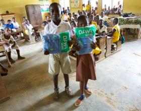 Source - © 2016 Sarah Hoibak/VectorWorks, Courtesy of Photoshare. Addo and Festus, students at Amanhyia Catholic School in Ghana, receive long-lasting insecticide-treated bed nets (LLINs) from their teacher Justine Ayivor during the 2016 Ghana Primary School based distribution campaign.