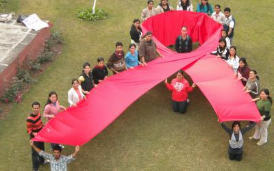 Source - © 2009 Gaurav Gaur, Courtesy of Photoshare. Description - Students of the Department of Social Work at Panjab University make a red ribbon to mark World AIDS Day in Chandigarh, India.