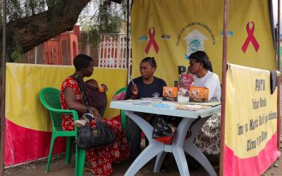 Source: Wayne Hoover. Description: A mother consults with health workers in Tanzania.