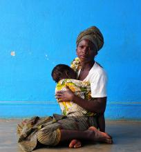Source - © 2017 Arturo Sanabria, Courtesy of Photoshare. Description - A woman breastfeeds her child while waiting for health services outside a health center in Nampula, Mozambique.