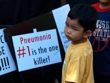 "Source - © 2008 Ferdinand G. Fuellos, Courtesy of Photoshare. Description - A child stands in front of a sign reading, ""Pneumonia #1 is the one killer!"" at the International Society of Tropical Pediatrics Congress in Philippines."