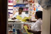 Source - PSI. Pharmacy workers discussing the various commodities available.