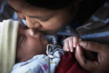 A mother kisses her infant in Chiangmai Province, Thailand. © 2010 Hansa Tangmanpoowadol, Courtesy of Photoshare